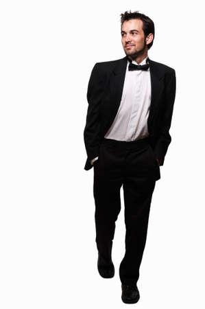 검은 턱시도 스테핑 착용 수염을 가진 매력적인 젊은 갈색 머리 남자의 몸 전체 스톡 콘텐츠