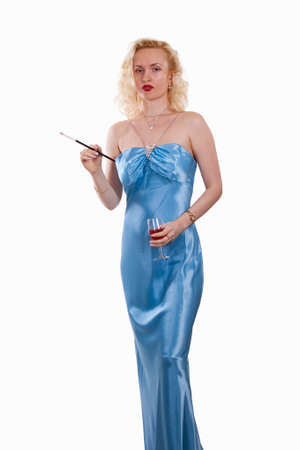 Attractive blond woman wearing light blue long satin evening gown holding a glass of wine and a cigarette in holder over white Stock Photo