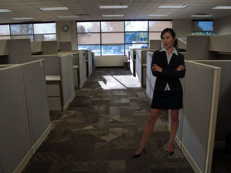 Full body of an attractive brunette Asian  woman wearing black business suit with skirt standing in aisle inside office building beside cubicles photo