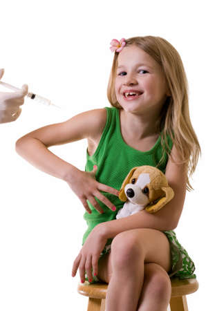 shot: Hand of nurse or doctor holding a syringe with little girl child sitting looking at needle