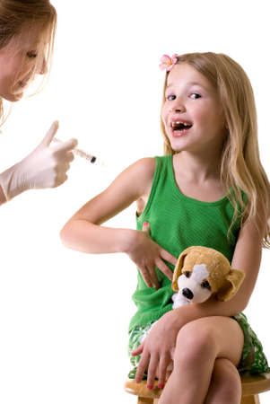 Female nurse or doctor holding a syringe with little girl child sitting looking at needle photo