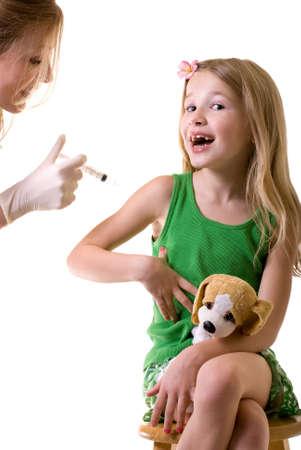 immunize: Female nurse or doctor holding a syringe with little girl child sitting looking at needle Stock Photo