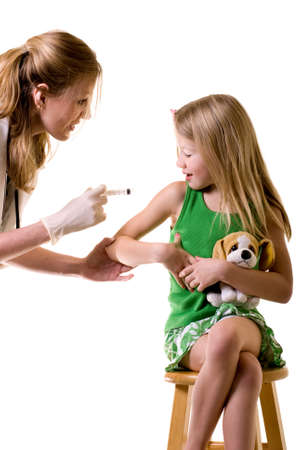vaccination: Female nurse or doctor holding a syringe with little girl child sitting looking at needle Stock Photo