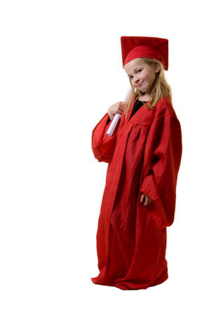 Cute little eight year old wearing red graduation cap and gown holding a diploma standing on white