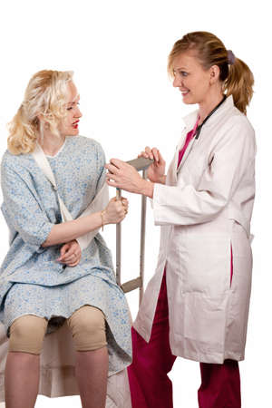Blond woman doctor standing beside female patient wearing an arm sling and holding a crutch photo