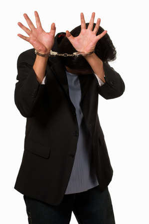 locked: Brunette man in handcuffs hiding his face Stock Photo