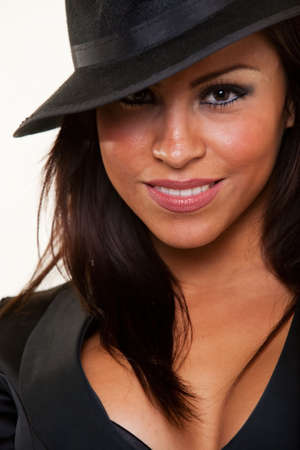 fedora hat: Close up of face of an attractive brunette hispanic woman wearing a black gangster style hat smiling Stock Photo