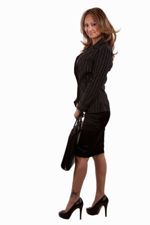 Full body of an attractive brunette Asian  woman wearing black business suit with skirt and holding a briefcase standing on white Stock Photo