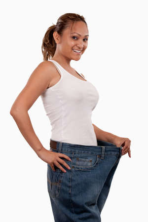 baggy: Attractive slim Asian woman smiling demonstrating weight loss by wearing an old pair of jeans and holding out to show how big the pants are Stock Photo