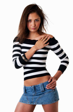 Fashion portrait of a pretty young Hispanic woman with long brown hair wearing striped black and white top and mini denim skirt over white
