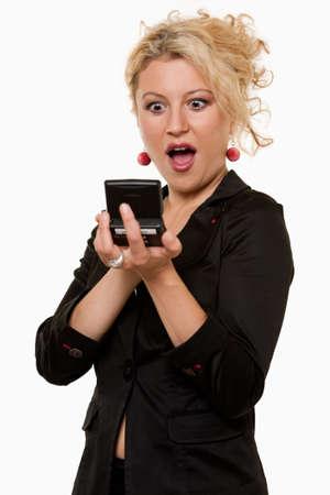 pager: Attractive blond business woman wearing business suit holding up and looking at a pager message with a shocked or surprised expression