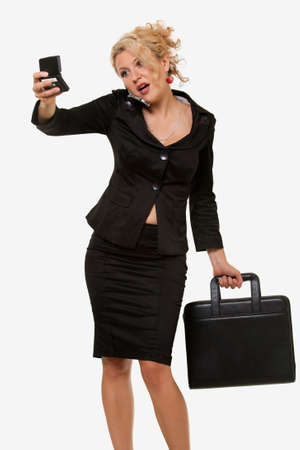black briefcase: Attractive curly hair blond business woman wearing business suit holding up a pager while carrying a black briefcase or portfolio