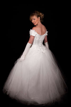 Full body of an attractive blond woman wearing white wedding gown with wide flowing skirt over black Imagens