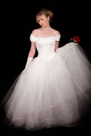 Full body of an attractive blond woman wearing white wedding gown with wide flowing skirt over black 版權商用圖片