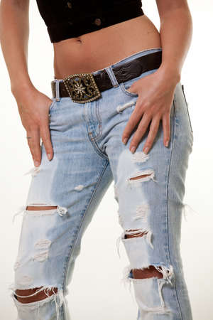 women in jeans: Bottom part of a womans body wearing ripped faded jeans with belt and buckle standing over white