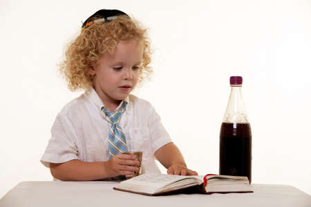 Portrait of a curly hair blond little three year old boy wearing white shirt and tie and a kippah jewish hat practicing the Sabbath ritual photo