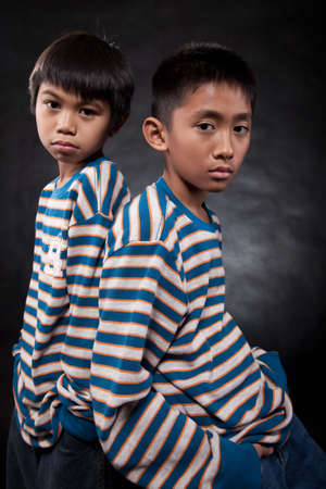fraternal: Two young eleven year old asian boys standing with backs together wearing matching shirts