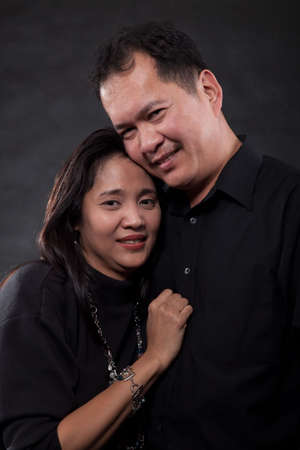 Portrait of middle age adult asian couple over black hugging