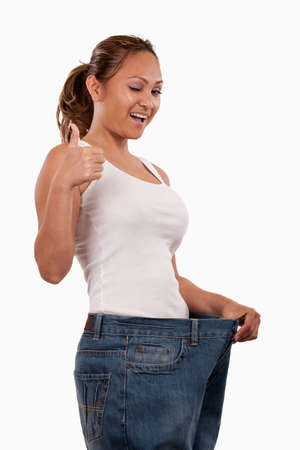 succeed: Attractive slim Asian woman smiling demonstrating weight loss by wearing an old pair of jeans and holding out to show how big the pants are winking with thumb up