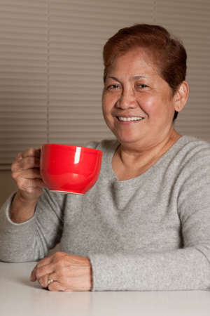 filipino: Senior asian woman sitting on a chair relaxing at home smiling holding a red coffee mug