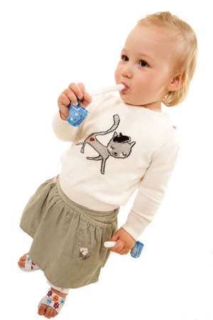 favor: Cute little blond hair baby girl standing on white while blowing on a party favor wearing skirt