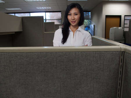Attractive brunette Asian  woman standing in cubicle inside office building photo