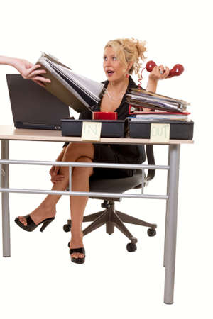 Blond woman secretary sitting at desk with over flowing in box with a person handing more work with a overwhelmed expression