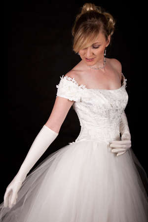 lace gloves: Attractive blond woman wearing white wedding gown with wide flowing skirt over black Stock Photo