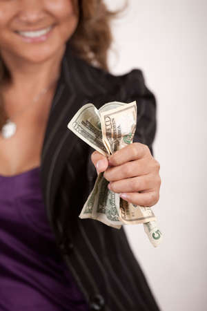 Smiling woman in business suit holding our arm with a bunch of crumpled dollar bills in fist