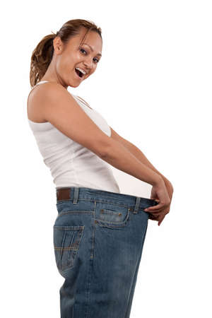 succeed: Attractive slim Asian woman smiling demonstrating weight loss by wearing an old pair of jeans and holding out to show how big the pants