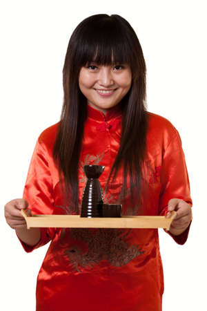 tradition: Attractive asian woman wearing orange satin culture attire holding a tray with a saki cups and jug