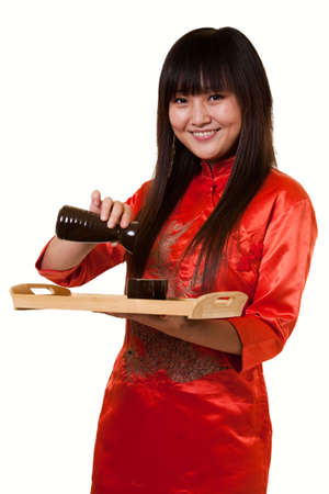 saki: Attractive asian woman wearing orange satin chinese attire holding a tray with a saki cups and jug