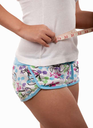 Womans body wearing shorts using a tape measure around waist to demonstrate weight loss