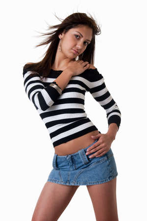 mini: Fashion portrait of a pretty young Hispanic woman with long brown hair wearing striped black and white top and mini denim skirt over white