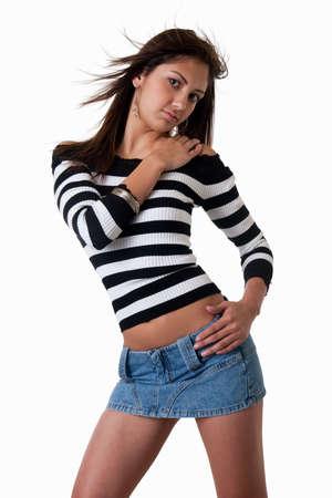 mini jupe: Mode portrait d'une jeune femme d'origine hispanique aux longs cheveux bruns portant des rayures noires et blanches en haut et mini jupe de denim blanc