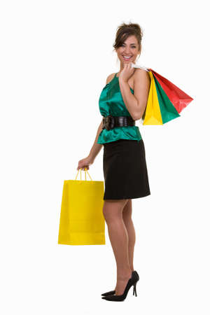 Full body of a brunette woman holding up a bunch of colorful shopping bags standing on white background