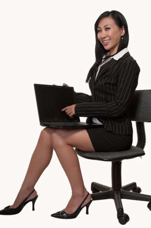 Full body of an attractive Asian woman wearing black business skirt suit sitting sideways on chair and holding and pointing at laptop screen
