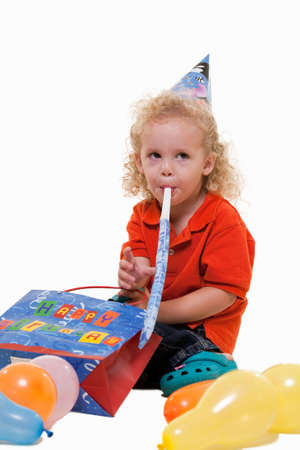 Adorable little three year old boy wearing party hat sitting with balloons blowing on a party favor photo