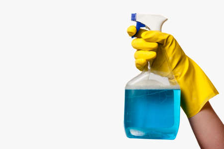Isolated hand wearing yellow cleaning glove holding a bottle of blue spray cleaner on white Stok Fotoğraf