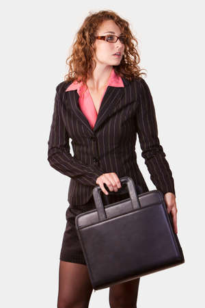 Attractive curly hair business woman with eyeglasses wearing professional suit standing on white holding a black briefcase