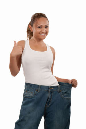 Attractive slim Asian woman smiling demonstrating weight loss by wearing an old pair of jeans and holding out to show how big the pants