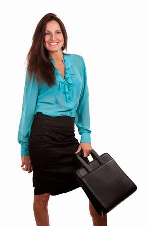 Brunette woman wearing aqua blue blouse and black skirt holding a briefcase smiling standing on white