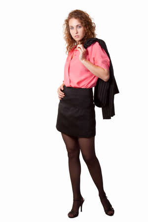 Full body of an attractive curly hair woman wearing black skirt and pink blouse with blazer over her shoulder