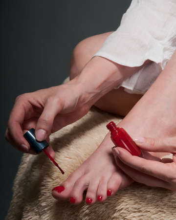 Legs of a woman holding a nail polish jar painting toes red photo