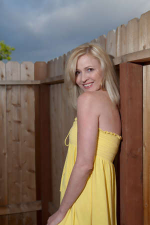 Attractive blond woman in yellow dress standing outside leaning on wooden fence photo