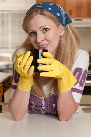 Blond caucasian woman wearing a bandana leaning on counter in kitchen holding a cup of coffee photo