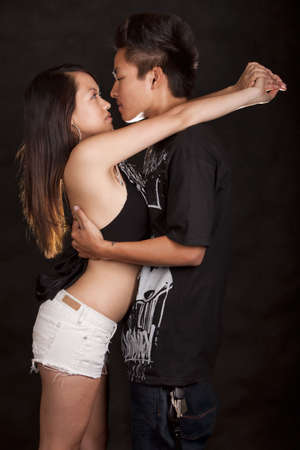 Young asian couple touching about to kiss