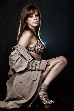 trench: Young caucasian female model wearing sexy attire with trench coat Stock Photo