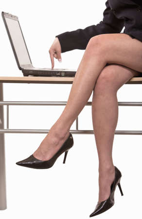 cross leg: Businesswoman sitting on table typing on computer