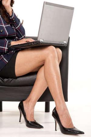 laptop: Businesswoman legs with laptop wearing heels Stock Photo
